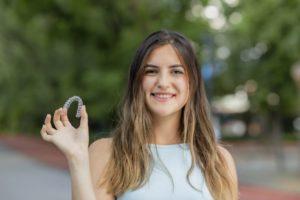Smiling woman holding Invisalign in marlborough