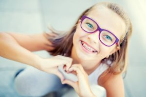 Smiling young girl with pediatric braces in Marlborough making a heart with her hands