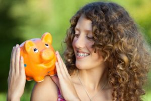 Smiling woman with orthodontic treatment holding piggy bank